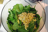 Place spinach, lemon juice, lemon peel and pine nuts in food processor.