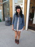The denim shirt, bow headband, and key necklace are quirky touches.