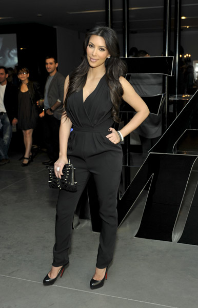 Kim Kardashian worked her black jumpsuit and black stud clutch.