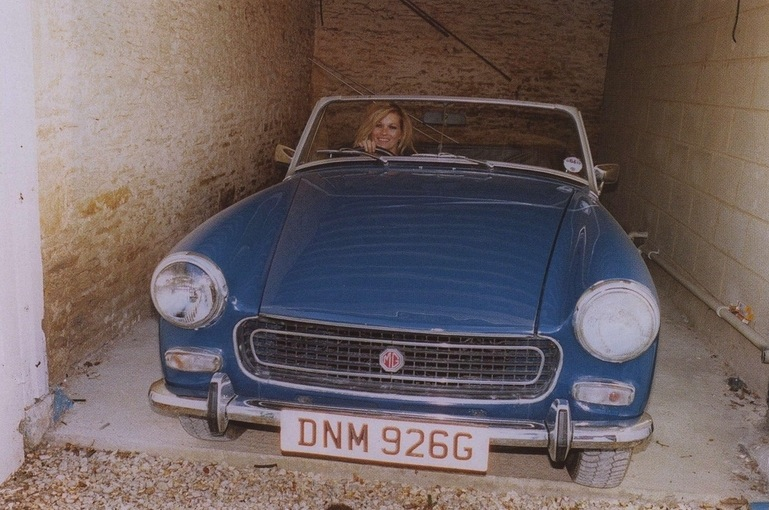 Taking her blue vintage car for a spin.