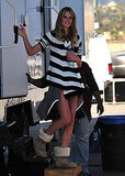 Coming out of her trailer in a striped cardigan and fuzzy boots.