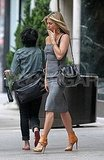 Jennifer Aniston paired nude heels with her gray dress.