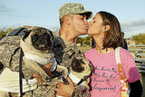 Army Spc. Leo Leroy gets a kiss from Regina Leroy and maybe some licks from dogs Yoshi and Bruiser at Fort Hood, Texas, on Nov. 28, 2009.
