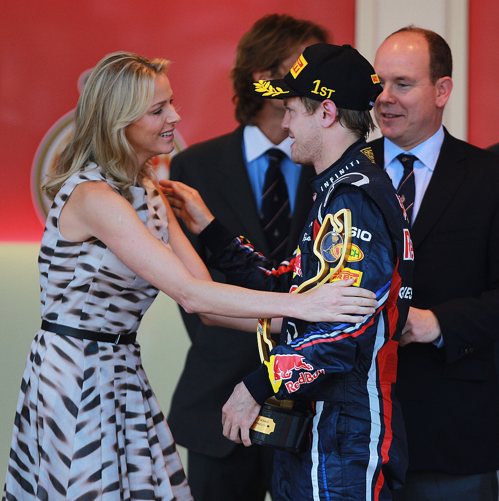 Sebastian Vettel of Germany receives the winner's trophy from Prince Albert II of Monaco and his girlfriend, Charlene Wittstock, in May 2011.