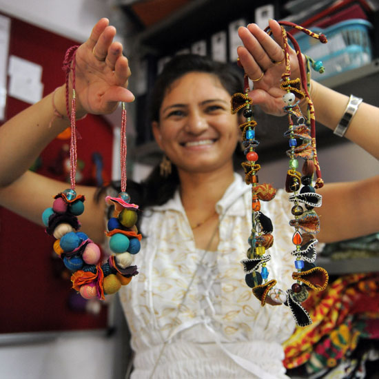 An Indian woman holds necklaces made from waste material.