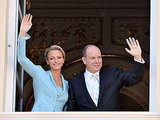 Smiling Princess Charlene of Monaco and Prince Albert II of Monaco wave for the crowd.