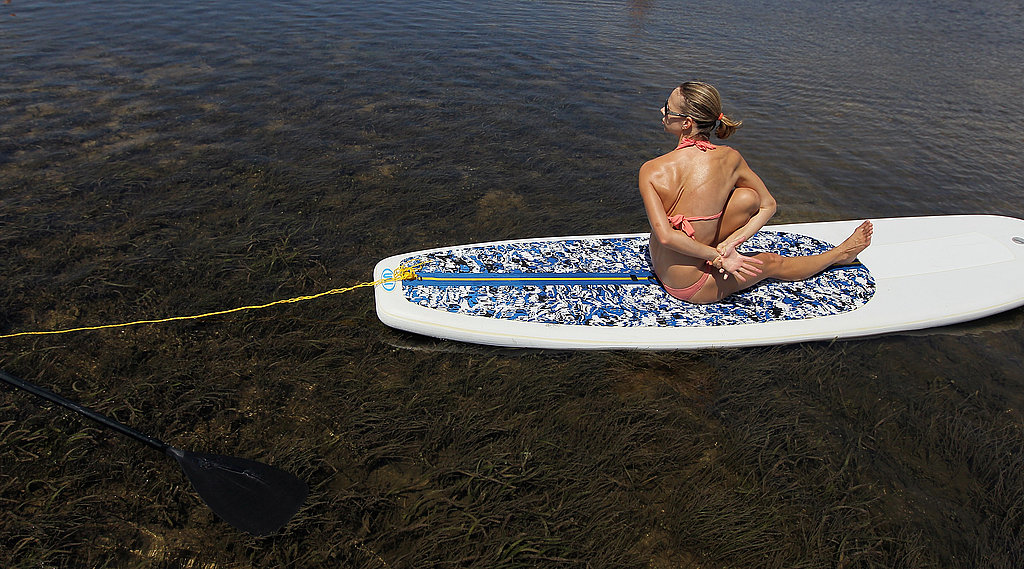 A woman stretches during the paddleboard yoga class.
