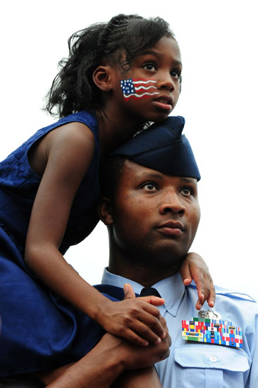 A serviceman and his daughter listen to President Obama at the White House's Fourth of July BBQ.