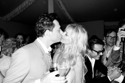 Kate Moss and Jamie Hince kiss after cutting the cake at their wedding.