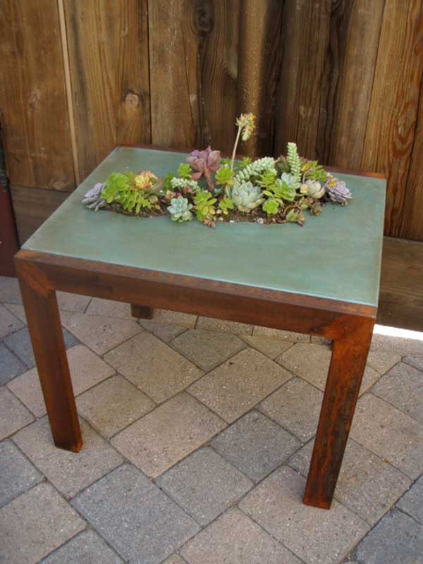 Concrete tabletops and succulents create a gorgeous contrast in materials. This table was made by concrete and metal artisan Five Feet From the Moon.