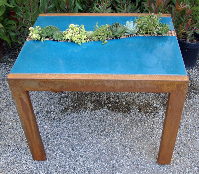 The blue shade of this concrete tabletop, also made by  concrete and metal artisan Five Feet From the Moon, really makes the plants pop.