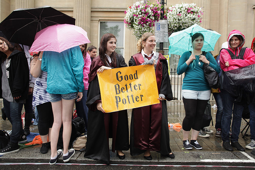 Two fans hold a sign in wizard robes at the Harry Potter and the Deathly Hallows Part 2 premiere.