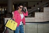 Kim Kardashian carries a yellow Hermes bag.