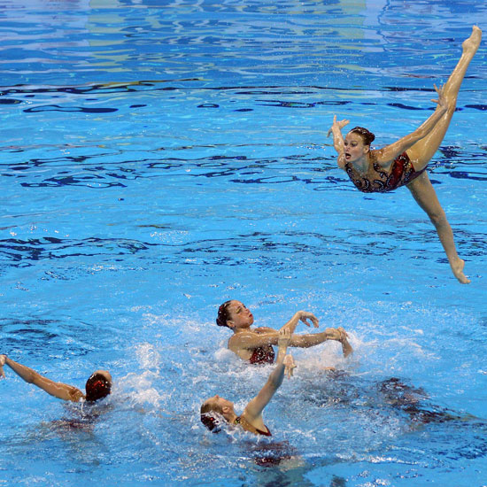 A Russian synchronized swimmer flies in the air at the FINA World Championships.