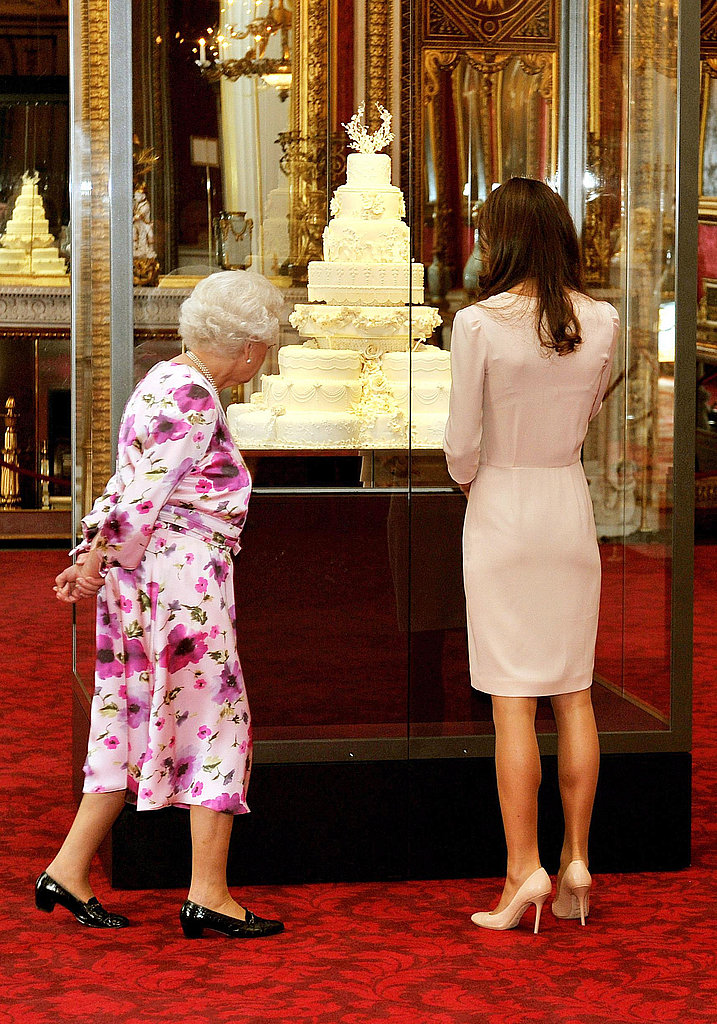 Kate Middleton and Queen Elizabeth view a replica of the royal wedding cake.