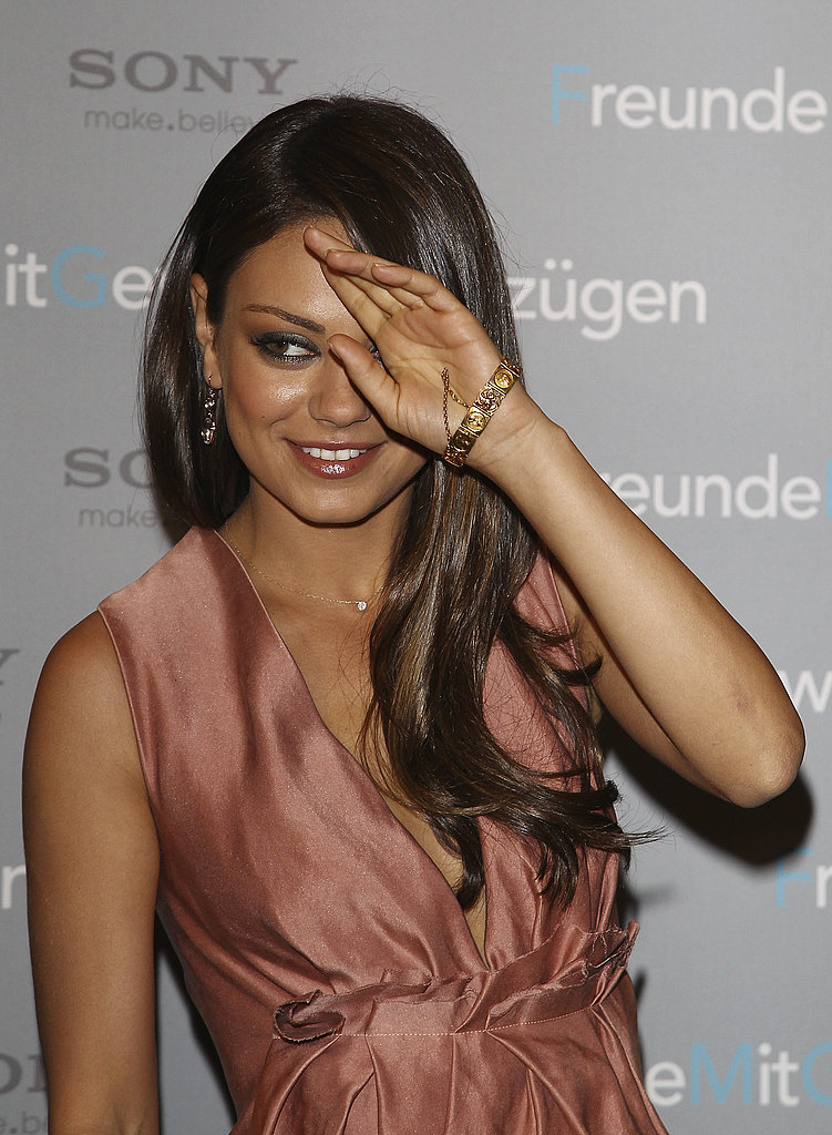 Mila Kunis swept the hair from her eyes.