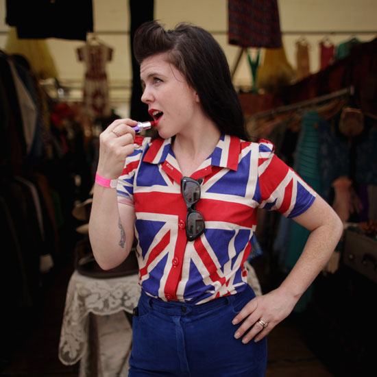 A girl puts on ruby-red lipstick to match her British flag top.