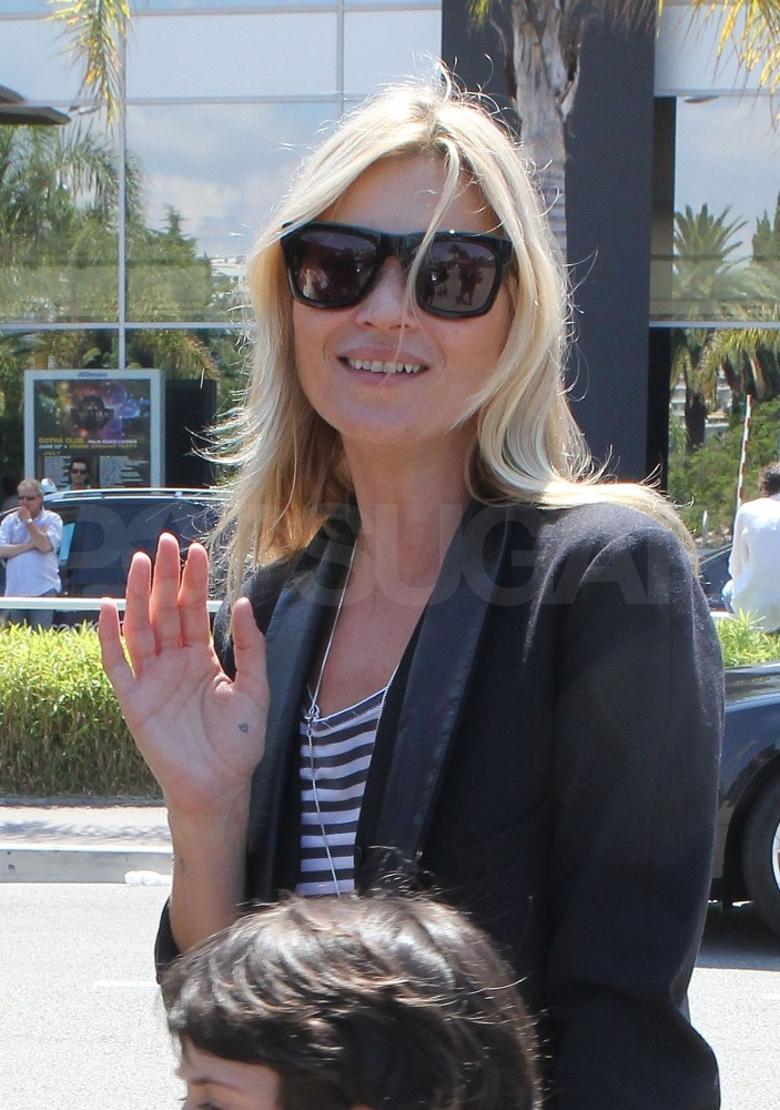 Kate Moss waves to photographers.