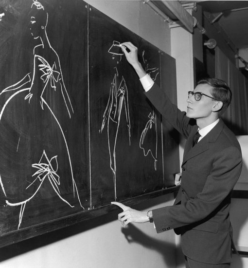 Yves Saint Laurent began his career at the House of Dior — here he's shown working on new designs in Paris in 1960.