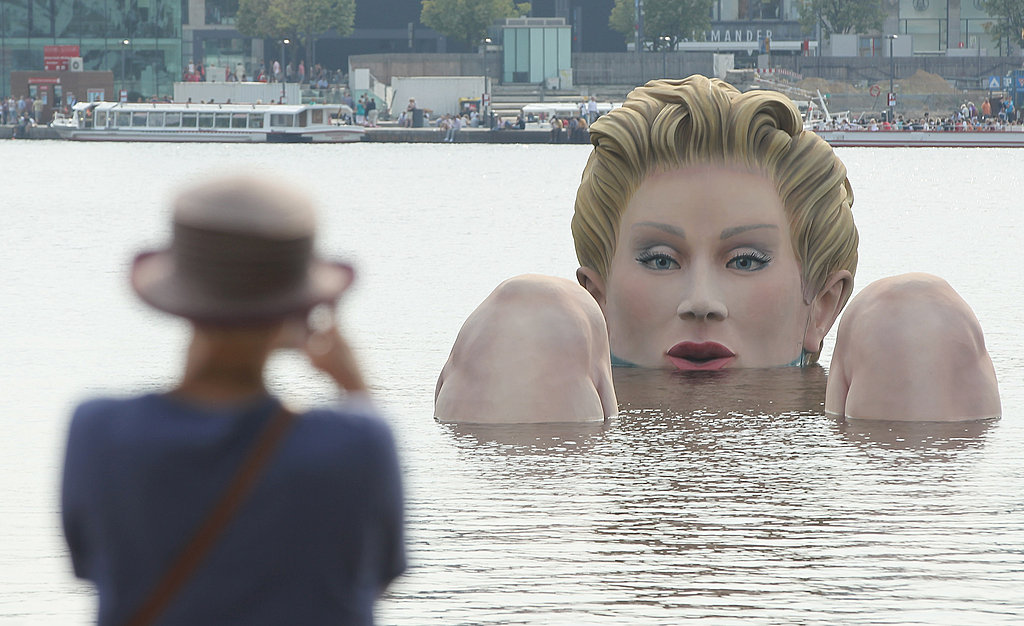 "A woman snaps a pic of lake-bound ""Die Badende (The Bather)"" in Hamburg, Germany."