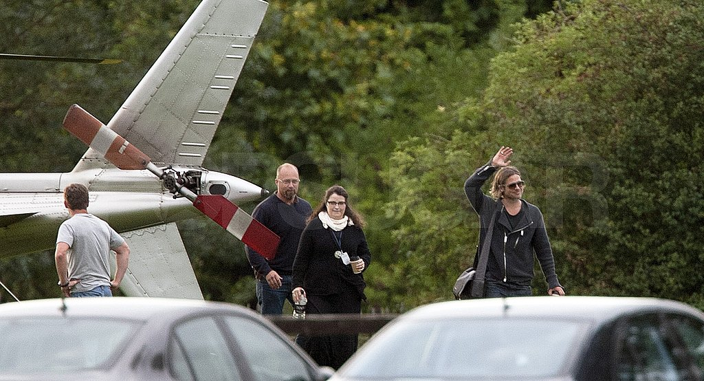 Brad Pitt waves to friends arriving in Richmond, England.