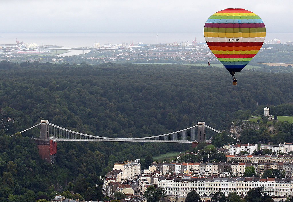 A striped hot-air balloon sits quietly over the city.