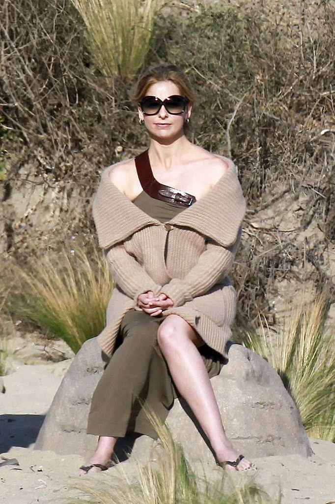 Sarah Michelle Gellar sat on a rock.