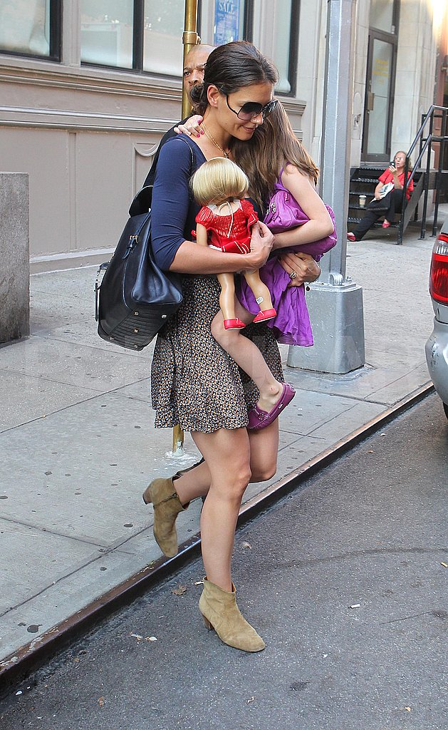 Katie Holmes carries Suri Cruise and a baby doll.