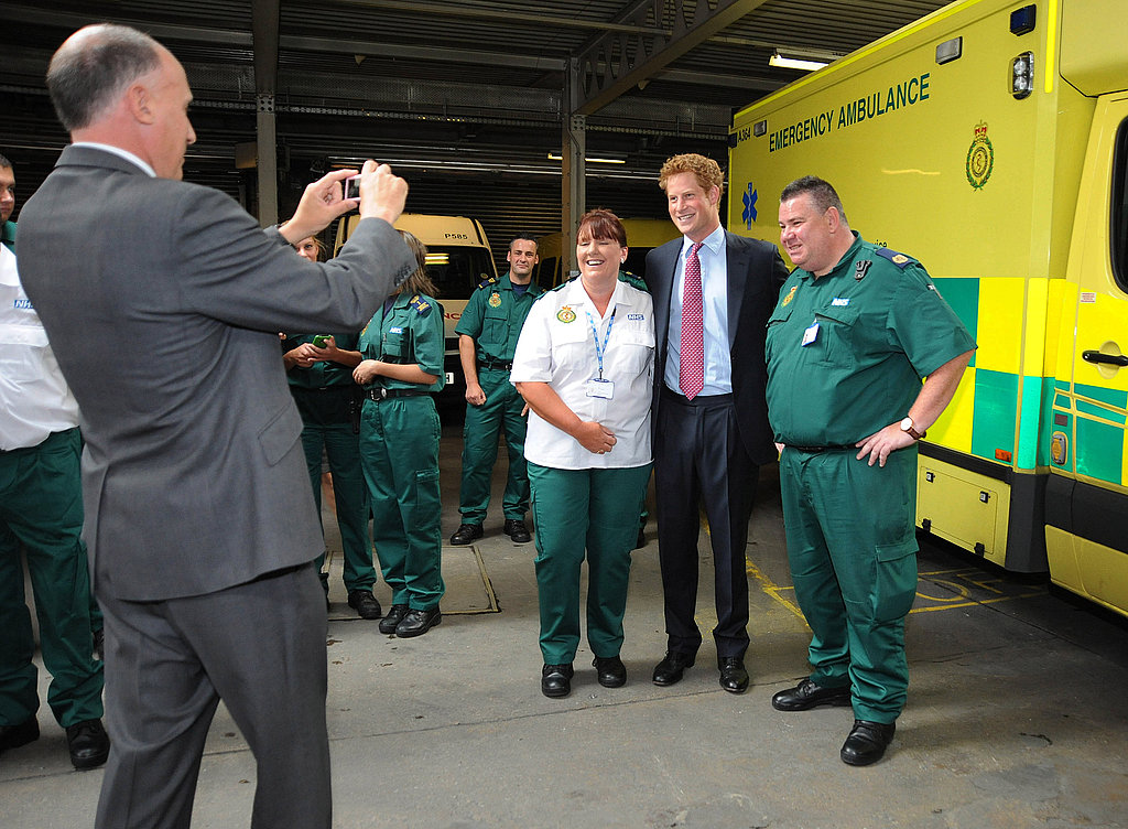 Prince Harry gets close to a couple of ambulance workers for a photo.