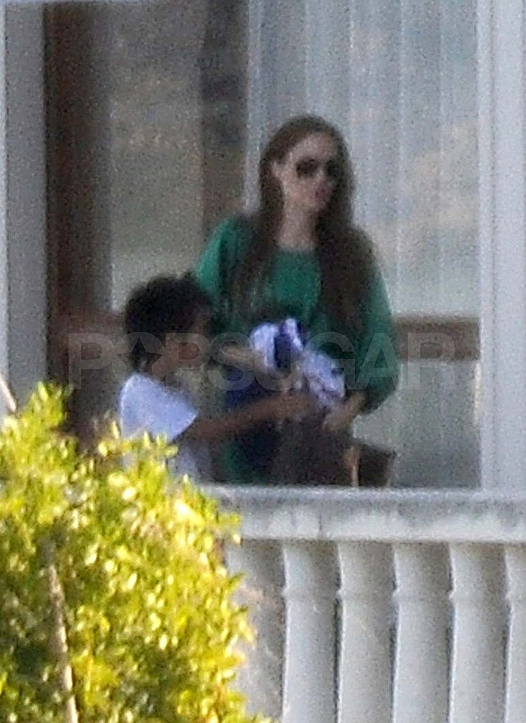 Angelina Jolie wearing green with Maddox.