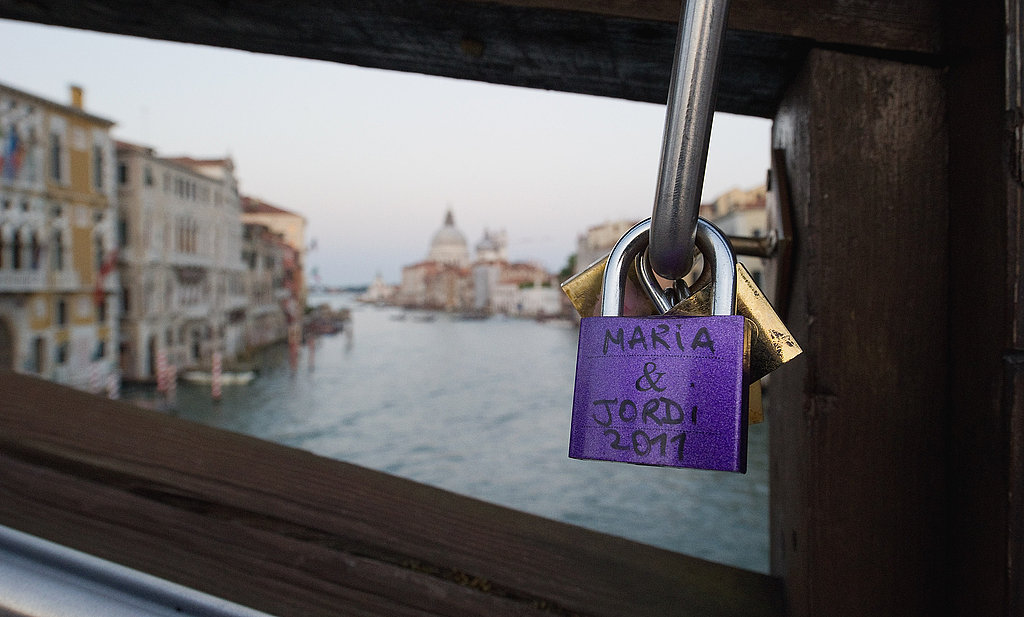 Love padlocks are clustered together on a railing on Ponte dell'Accademia in Venice, Italy.