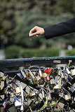 A woman throws away the key on a bridge in Paris.