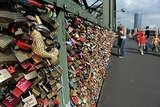People look at the Liebesschloesser, or love padlocks, attached to a fence on Hohenzollernbruecke bridge in Cologne, Germany.