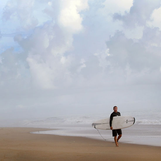 A surfer walks the beach in Kitty Hawk, NC.