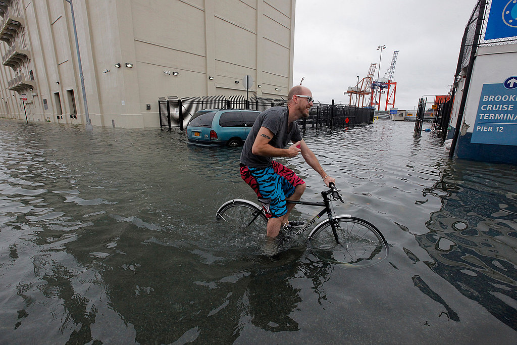 A guy cycles through the flooded streets in New York.
