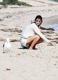 Selena took a seat on the sand next to Justin.