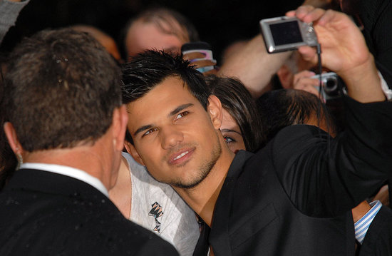 Taylor Lautner takes pictures with fans in London.