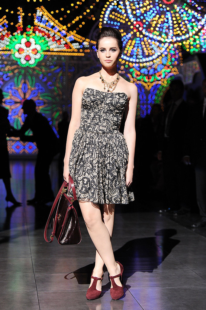 Felicity Jones donned a strapless printed dress and red suede pumps at the Dolce & Gabbana show.