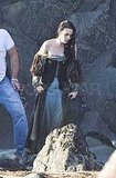 Kristen hiked up the hem of her dress walking along the beach.