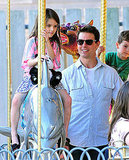 Suri Cruise balanced her stuffed panda on a carousel.