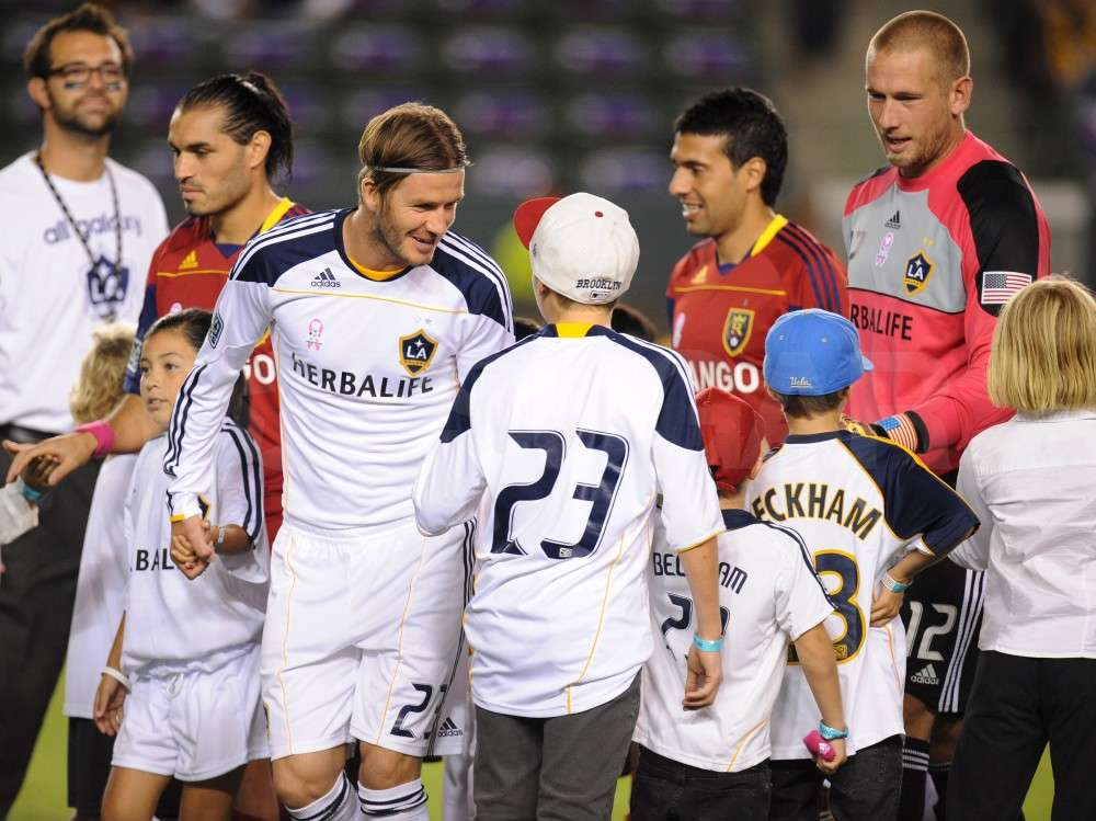 David Beckham gave Brooklyn Beckham a high-five as Cruz Beckham and Romeo Beckham stood nearby.