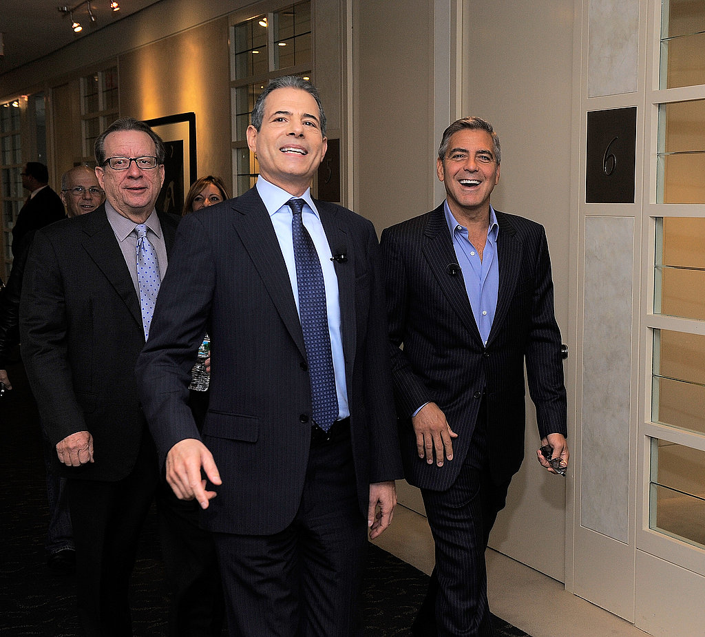 George Clooney was escorted to a talk by John Huey and Rick Stengel.