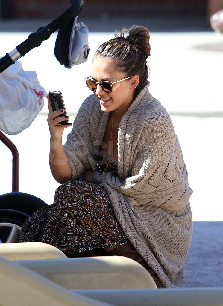 Jessica Alba snaps pictures at a park.