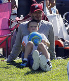 Cruz Beckham took a seat on David Beckham's lap while watching Romeo and Brooklyn play soccer.