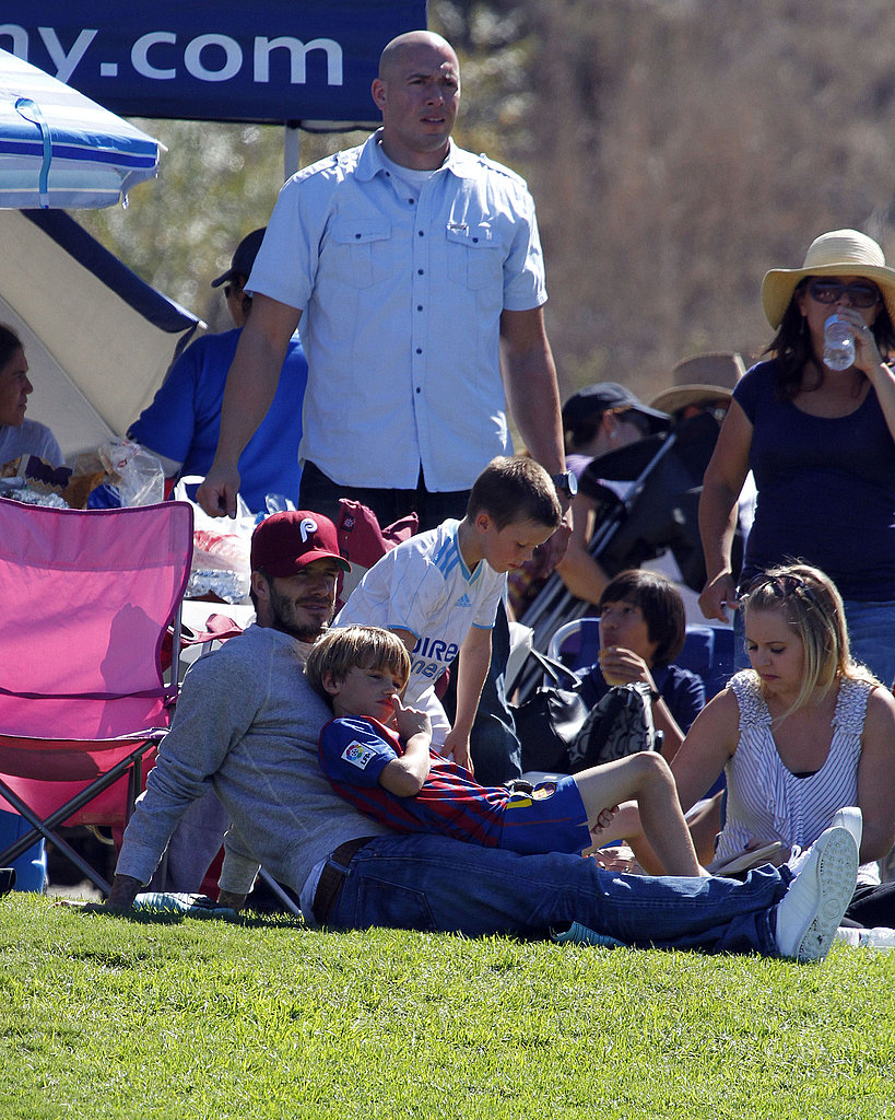 Romeo Beckham reclined on David Beckham and Cruz Beckham watched his brother, Brooklyn play soccer.