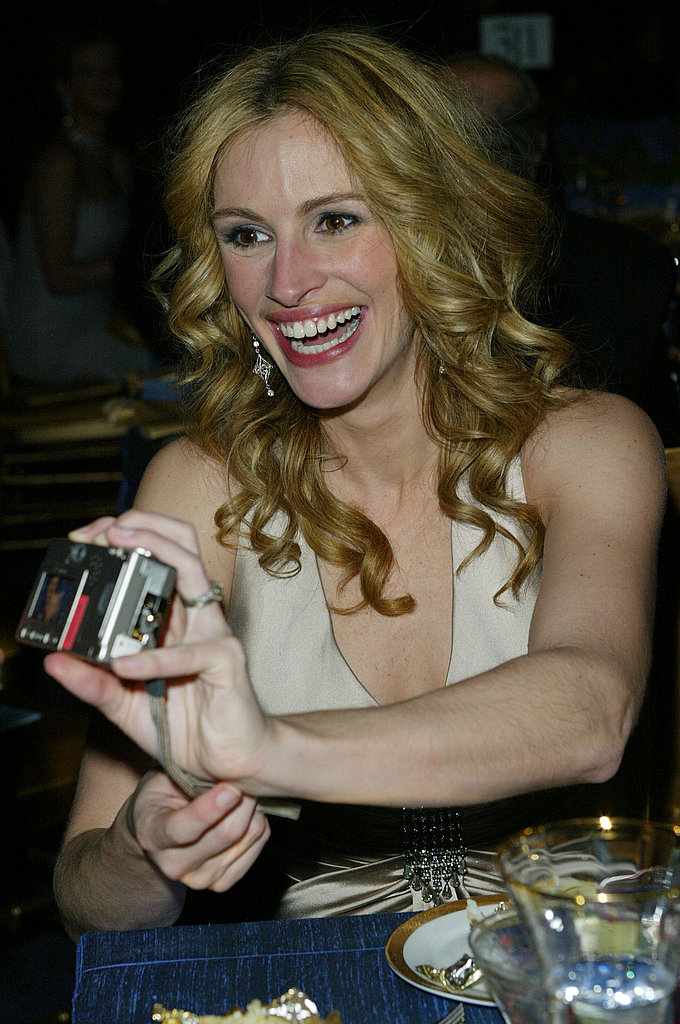 At the Academy Awards Governors Ball in 2004, Julia Roberts got a kick out of her own photos.
