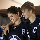 Justin wrapped an arm around Selena during the hockey game.