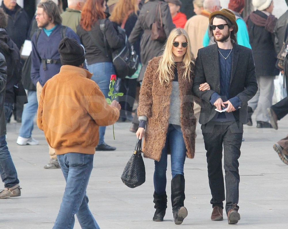 Sienna Miller took Tom Sturridge's arm.