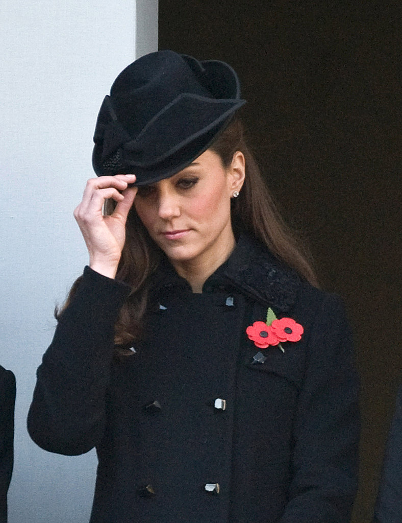 Kate Middleton adjusted her Jane Corbett fascinator.
