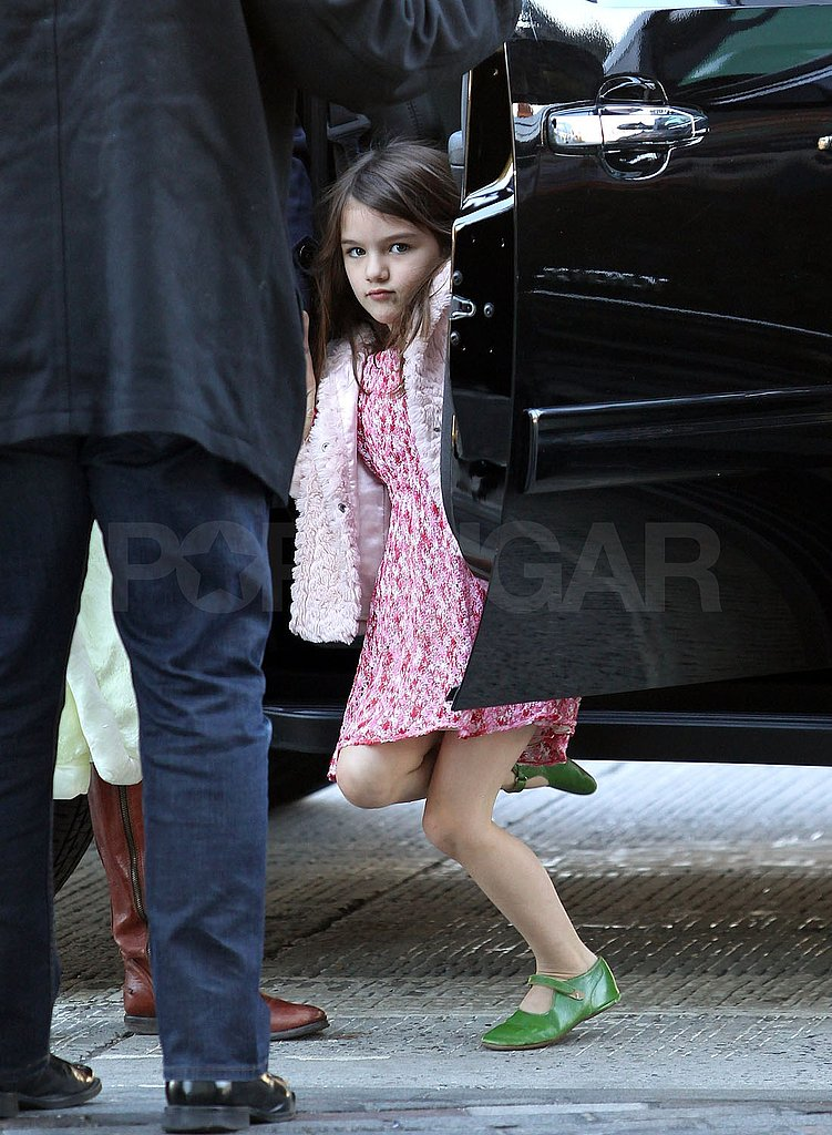 Suri Cruise got help jumping out of the black SUV.